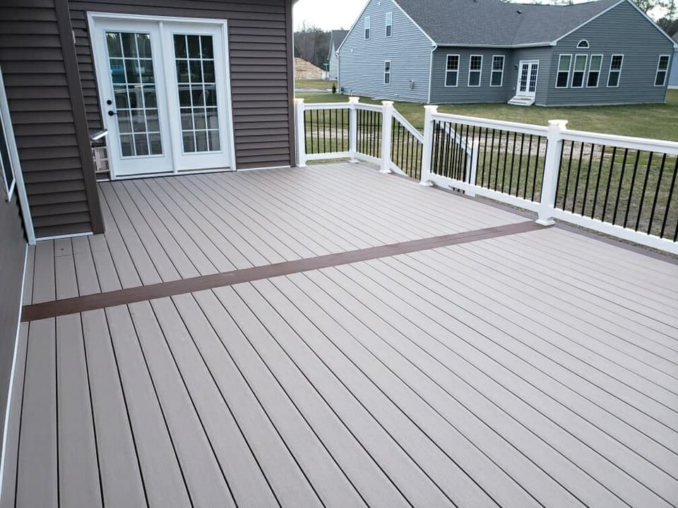 beautiful ground level light brown deck attached to back of house