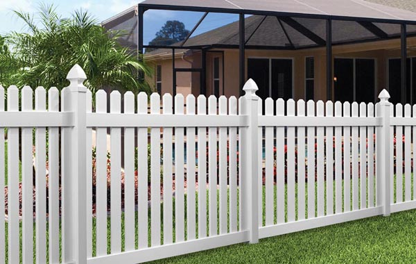 tall white picket fence backyard with grass shrubs